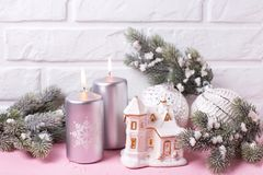 Decorative house, silver candles, branches fur tree and balls. On pink background against white wall. Selective focus royalty free stock photos