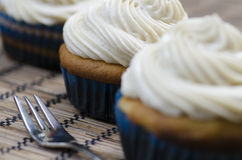 Decorative iced cupcakes. Three decorative iced cupcakes topped with white twirled icing on a placemat with a fork, low view angle with shallow depth of field Royalty Free Stock Image