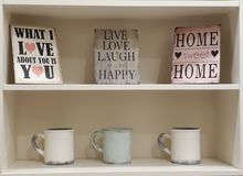 Decorative inspiring shelf. With mugs and signs for home royalty free stock photography