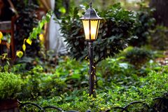 A decorative iron lantern tied with a garland. A decorative iron lantern tied with a garland illuminates a green garden with plants royalty free stock photography