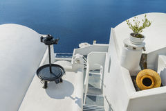 Decorative items adorn the roofs of traditional Greek houses and romantic staircase, leading to the Mediterranean sea. Santorini i Royalty Free Stock Image
