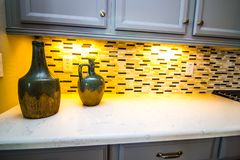 Decorative Jugs On Modern Kitchen Counter With Backsplash. Decorative Jugs On Modern Kitchen Counter With Backspash And Under Cabinet Lighting stock images