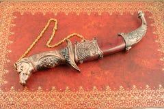 Decorative knife. Decorative asian knife with horses head and shield Royalty Free Stock Photo