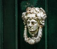 Decorative knocker. Made as a man`s head on a green door Stock Photo