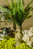 Decorative lamp with ferns and green stone and paper roses on a linen background with kerosene lamp. Royalty Free Stock Photography
