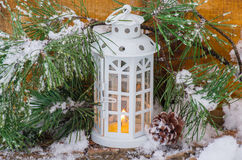 Decorative lantern burning in the snow with a conifer branch. In winter day stock photography