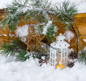 Decorative lantern burning in the snow with a conifer branch. In winter day royalty free stock photography