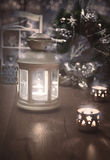 Decorative lantern, candles and Christmas decoratons on wood, te Stock Image