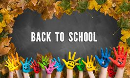 Decorative leaves and a blackboard with many painted kid hands stock photos