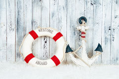 Decorative lifebuoy, anchor and starfish sea shells over wooden blue background.  Stock Photos
