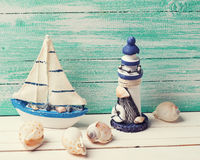 Decorative lighthouse,  sailing boat and marine items on wooden Royalty Free Stock Photo