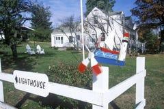 Decorative lighthouse weathervane on white picket fence by a white house, MI Royalty Free Stock Photos