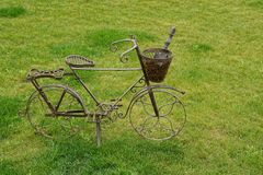 Decorative metal bicycle with basket and scoop standing on the lawn Royalty Free Stock Photos