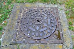 Decorative metal forged sewer hatch cover in green grass, top view close up royalty free stock photo