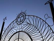 Decorative metal gates. Exterior of decorative metal gates with sun emblem; blue sky background Royalty Free Stock Photo