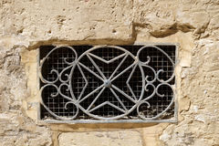 The decorative  metal ventilation grill in form of Maltese cross. The decorative  metal ventilation grill in form of 8-pointed Maltese cross in a stone wall Royalty Free Stock Photo