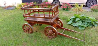Decorative, miniature wooden cart on the lawn with green grass. Landscape decoration. royalty free stock images