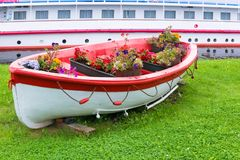 Decorative Model Old wooden oar boat full of flowers. Decorative Vintage Model Old wooden oar boat full of flowers. Landscaping Stock Photography
