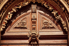 Decorative molding and carved wood with faces on the facade of house Stock Photography