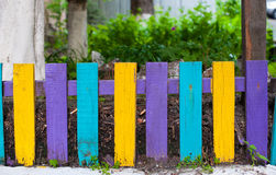 Decorative multicolored wooden fence near the house Stock Images