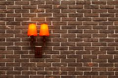 Decorative, neat wall made of brown ceramic bricks and wall lamps with orange shades. Modern imitation of the old brickwork. A fragment of the interior inside Stock Photography