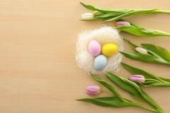 Decorative nest with dyed Easter eggs and spring flowers on table royalty free stock photo