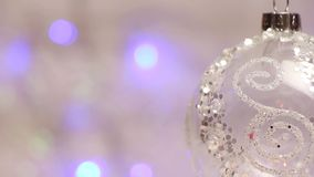 Decorative New Year`s ball rotates against the background of blue shimmering lanterns,midle-scale plane stock footage