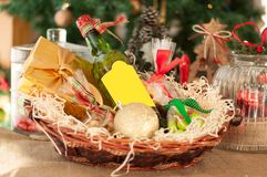 Decorative New Year`s gift baskets with a set of sweets and alco. Hol on a wooden table on a Christmas tree background Stock Photo