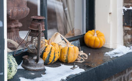 Decorative objects on a windowsill in wintertime. A rusty old oil lamp and some yellow pumpkins on a windowsill of an old house in a small Dutch village. It is royalty free stock photos