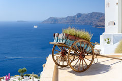 Decorative old cart with flowers on a roof terrace in Oia, Santorini Royalty Free Stock Photos