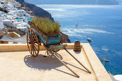 Decorative old cart with flowers on a roof terrace in Oia, Santorini Stock Photo