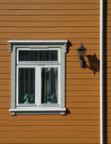Decorative old window on brown wall. Beautiful window and a lantern. House in Norway Royalty Free Stock Image