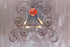 Decorative ornament of metal branches, leaves and a red rose on stock images