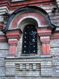 Decorative ortodox russian style close up view arc window. Beautiful russian style close up  view of brick wall arc window with two columns and forged metal Stock Image