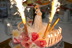 Decorative pair of newlyweds with candles on a wedding cake Royalty Free Stock Photos