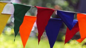 Decorative party multicolored striped pennants triangular flags on a two rope, closeup stock photography