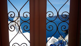Decorative patterned door in Santorini - focus in the foreground. In the background the blue sea Royalty Free Stock Image