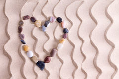 Decorative pebble heart on golden beach sand. Decorative pebble heart of waterworn alluvial quartzite, agate and basalt stones symbolic of love and romance on royalty free stock photos