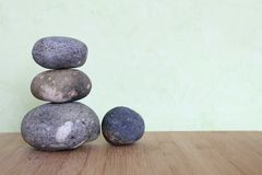 Decorative pebbles stacked in a Zen life fashion on a bamboo wooden board on a green Royalty Free Stock Photography