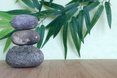 Decorative pebbles stacked in a Zen life fashion on a bamboo wooden board on a green and foliage background Royalty Free Stock Photo