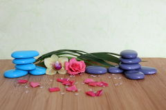 Decorative pebbles stacked in a Zen life fashion on a bamboo wooden board with a pink flower and an orchid on a green background Stock Photo