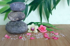 Decorative pebbles stacked in a Zen life fashion on a bamboo wooden board  with a pink flower and an orchid on a green and foliage Stock Photos