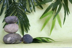 Decorative pebbles stacked in zen life fashion on green background Stock Photo