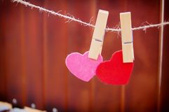 Two hearts hang on clothesboards on a wooden background stock image