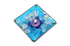 Decorative piece with lit candle. And decorative stones isolated over white Stock Image