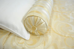 Decorative pillow-cushion of golden fabric on the bed. Closeup Stock Photography