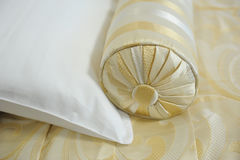 Decorative pillow-cushion of golden fabric on the bed. Closeup Royalty Free Stock Images