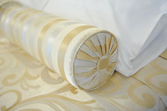 Decorative pillow-cushion of golden fabric on the bed. Closeup Royalty Free Stock Photos