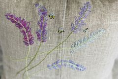 Decorative pillow made of linen fabric with colorful - yellow, violet, green, light blue - embroidery Stock Image