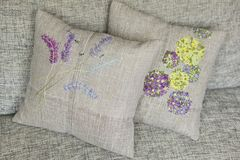 Decorative pillow made of linen fabric with colorful - yellow, violet, green, light blue - embroidery Stock Photography